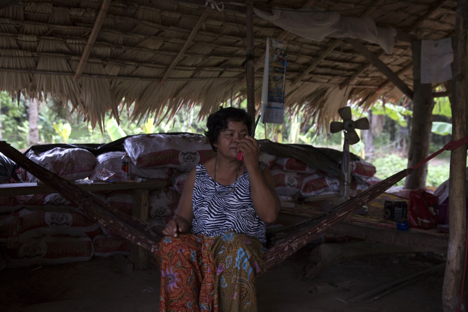 Pratep Pasaja, 54, makes a radio test whilst being security guard at one of the posts. Many villagers have walkie-talkies so they can communicate quickly if trouble arises. She will stay in the bunker all night until relieved by another team.