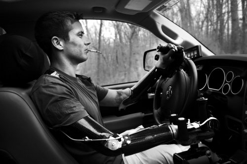Lake Ozark, Missouri, USA. 2014. Cpl. Todd Nicely driving his car, a custom made pick-up adapted to be driven with his prosthesis. He always smoke a cigarette every time he drives.