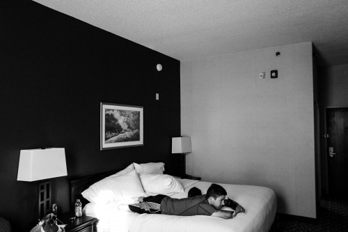 St. Louis, Missouri, USA, 2016. Todd Nicely, talking at the phone while he relaxes laying on a hotel bed before the charity event.
