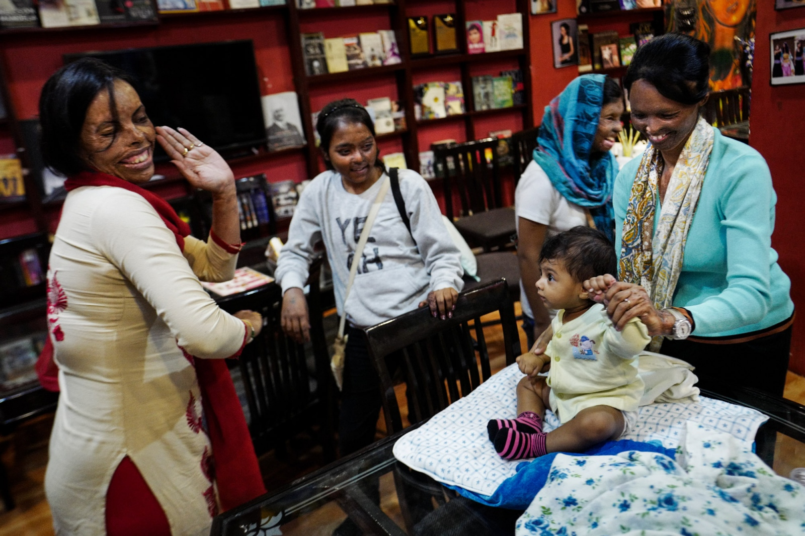 Agra, Uttar Pradesh, India. 29 October 2015. Soniya, on the left, plays with Pihu, the baby of Laxsmi, on the right, at the Sheroes Hangout Cafè. On the background two more activists: Dolly and Rupa, both Acid Attack Fighters. The women of the Sheroes Hangout decided to work at the cafè to raise awareness about this issue, but also to help other attacked women to start a new life.