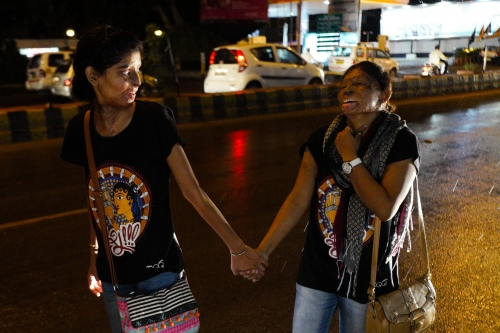 Agra, Uttar Pradesh, India. 28 October 2015. From the left, Ritu, 20, victim of a 18 people's plot, is the best friend of Rupa, 23, who is holding her hand. They live together in a safe house in Agra, India. Rupa is proud that after joining the Stop Acid Attack campaign, she stopped wearing the veil.
