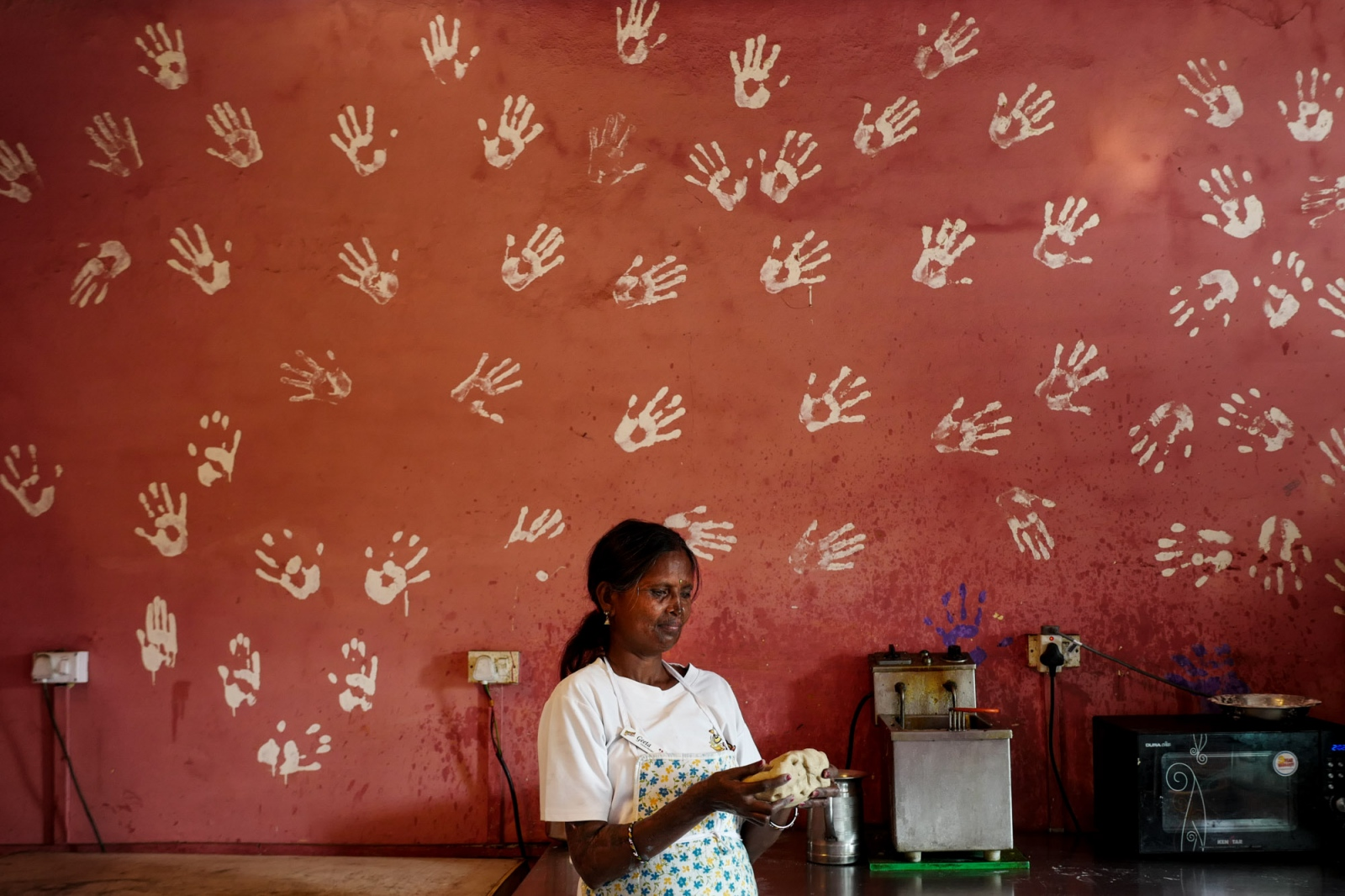 Agra, Uttar Pradesh, India. 02 November 2015. Gita, 45, the oldest survivor among the members of the Stop Acid Attack campaign, works in the kitchen at the Sheroes Hangout cafè. On the wall the imprints of all the survivors' hands. Gita poses for a portrait in the Kitchen where she's baking bread.