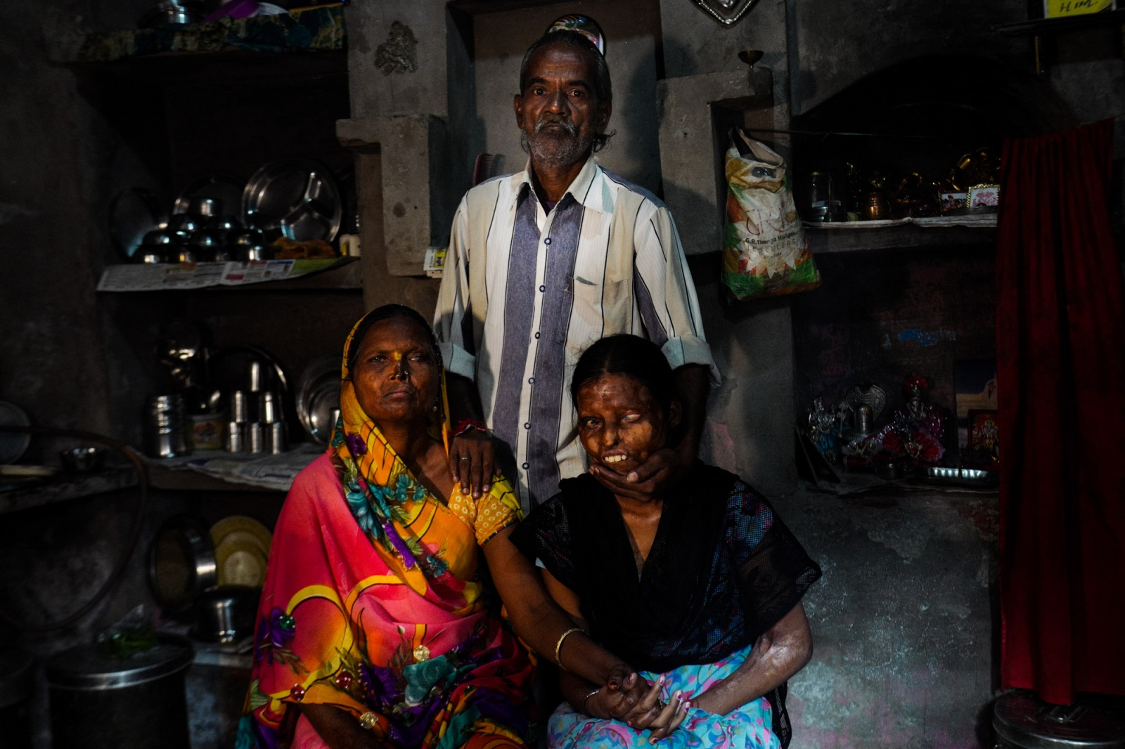 Agra, Uttar Pradesh, India. 04 November 2015. Gita (on the left) and her daughter Nitu posing for a portrait with Indrgit their husband and father. Gita is 45 and Nitu 24. Gita was only 24 years old when her husband Indrgit, a violent and alcoholic, attacked her out of jealousy. He threw acid at her, at Nitu and at Krishna, another daughter. Krishna died right after the attack, while Nitu, who was 3 years old back then, went almost completely blind. Indrgit was imprisoned, but after a while he asked for forgiveness. Gita forgave him and now they are still living together, sharing the same room. Gita and Nitu are both activist of the Stop acid attack association.