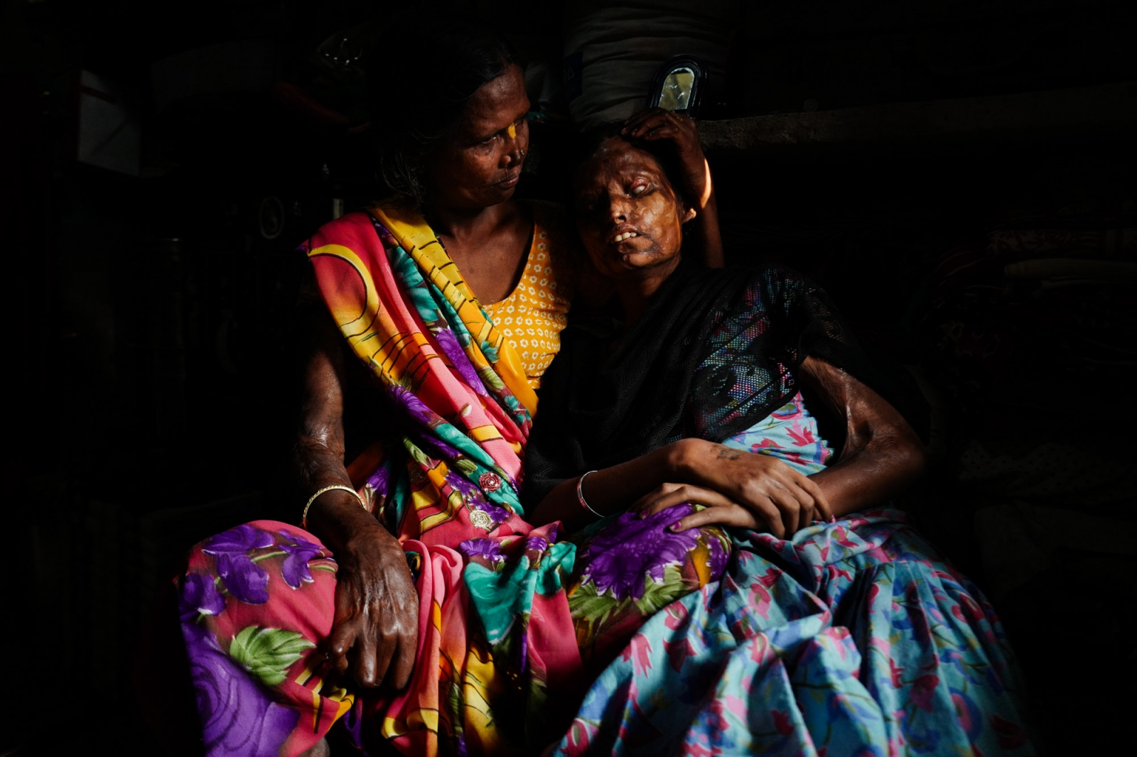 Agra, Uttar Pradesh, India. 04 November 2015. Gita, 45, on the left, holding her blind daughter Nitu, 24, posing for a portrait. They are both victims of Gita's husband's, a violent and alcoholic who, out of jealousy, threw acid at his wife, at Nitu and at Krishna, another daughter of 1 year old. Krishna died right after the attack, while Nitu, who was 3 years old back then, went blind. Gita and Nitu are both activist of the Stop Acid Attack campaign, and they work at the Sheroes Hangout Cafè.
