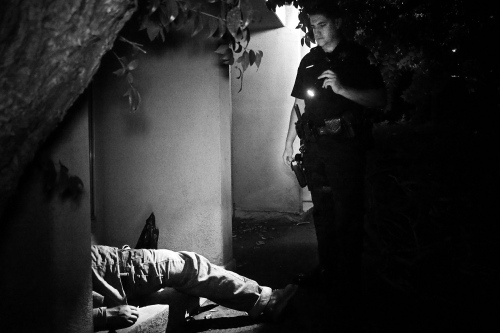 Fresno, California 2013 An officer of the Fresno police department carries out a body check of a man under the window of a dwelling.