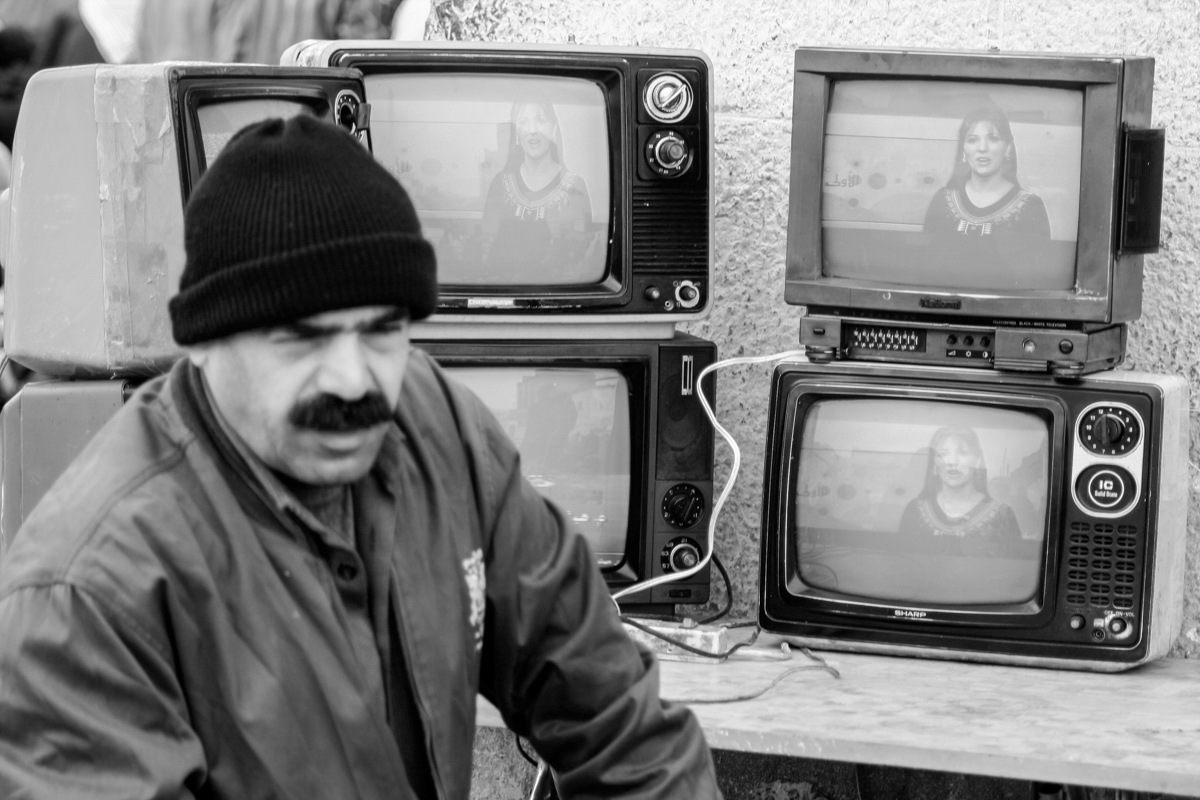 Somethings never change, Syrian public TV channel on used TVs for sale, street vendor, Damascus 2007.
