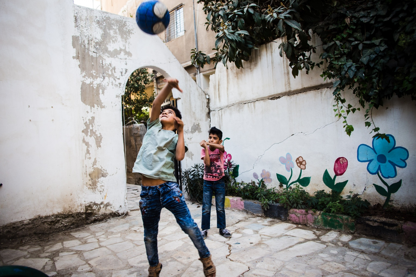 Two young Iraqi boys play with a ball in the playground area of Collateral Repair Project, a local NGO in Hashmi Shmali in East Amman.