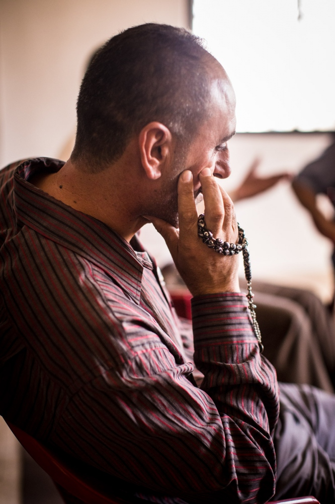 An Iraqi man sits during a therapy group, holding a string of prayer beads that are passed around in a circle, so each person gets to talk about a particular theme or experience.