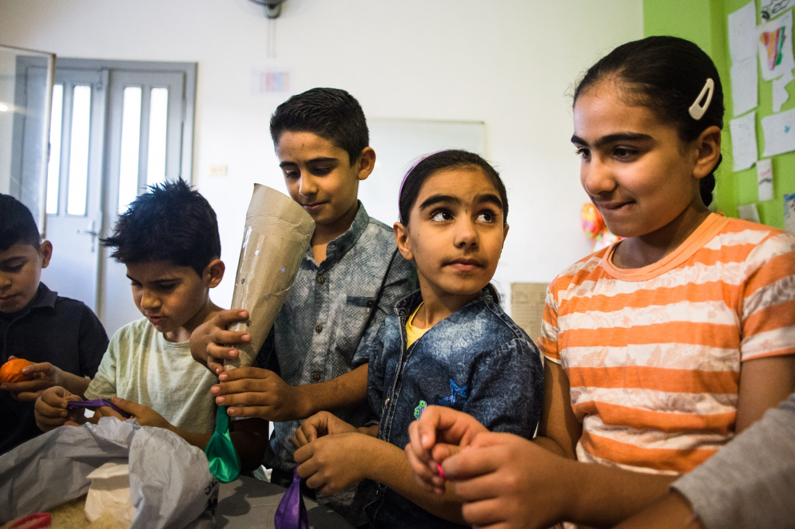 Iraqi and Syrian children work on an art project during an after school program. Collateral Repair Project, a local NGO in East Amman, provides classes, programs for children, and donations of food and other necessities to help Iraqi and Syrian refugees living in the neighborhood.