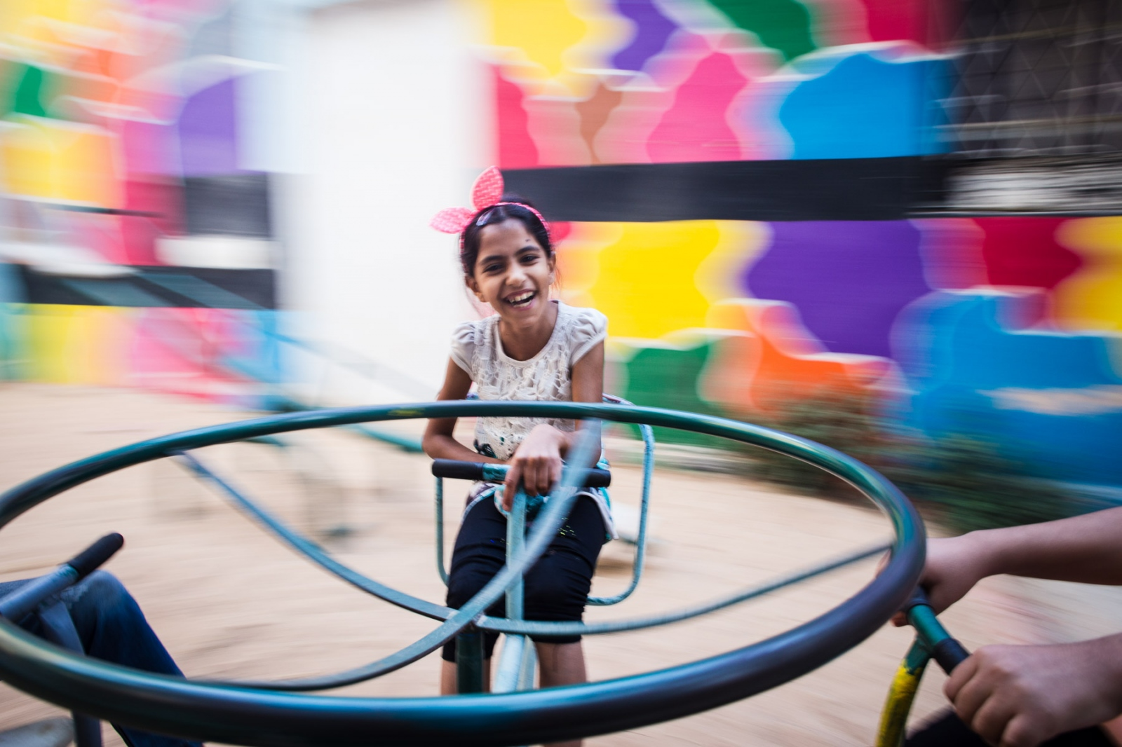 Tabarak, originally from Iraq, spins on a carousel in the playground area of Collateral Repair Project, a local NGO in East Amman.