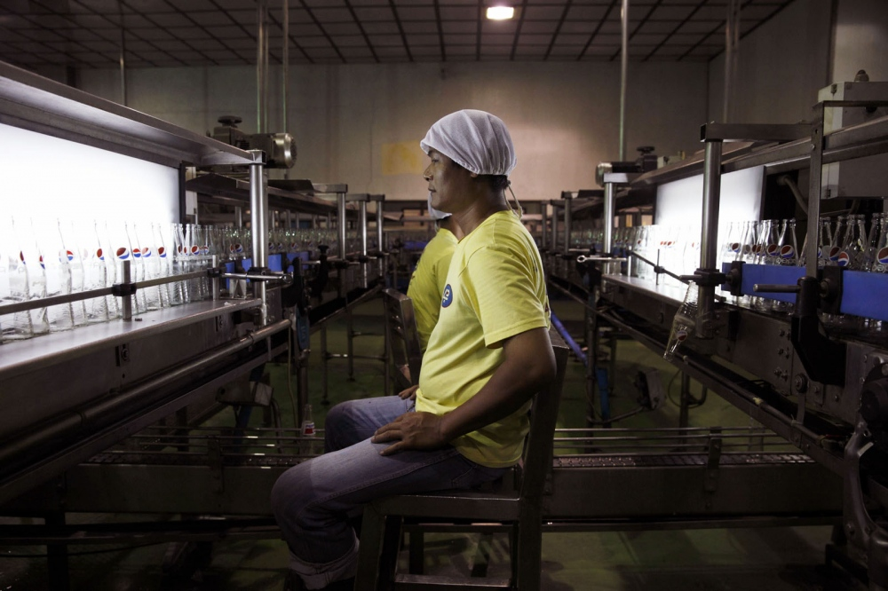 An employee of PepsiCo checks the quality of glass Pepsi bottles at a manufacturing plant on the outskirts of Manila, Philippines.