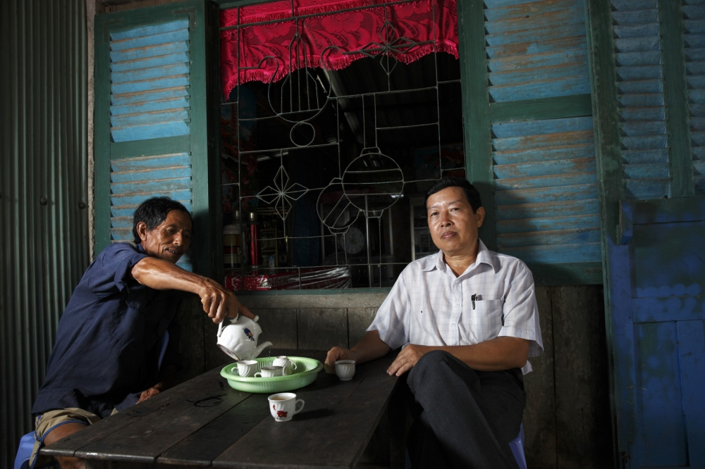 Dr Duong Van Ni of Can Tho University drinks tea with a farmer at his house. Dr Ni's research aims to help Vietnamese rice farmers in the Mekong Delta who's rice paddies suffer from an increased water salinity brought on by rising water levels. Mekong Delta, Vietnam.