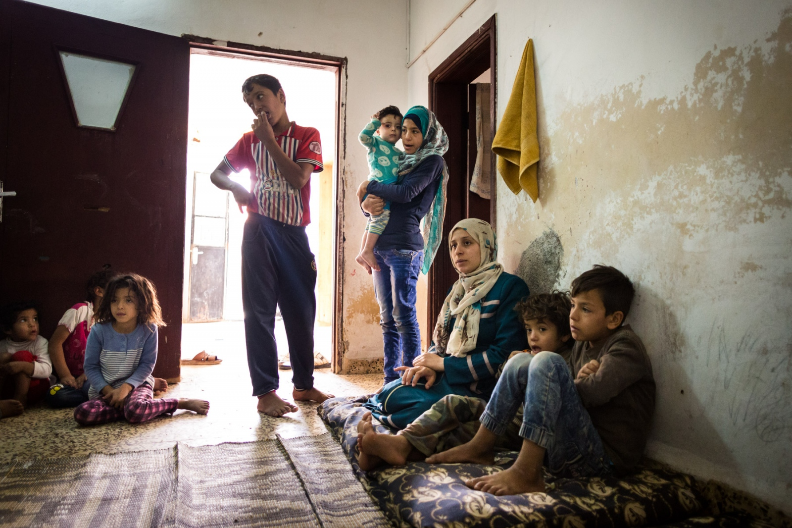 Abu Mohammed's family, originally from Aleppo, Syria, sits at home in Mafraq, Jordan, on Nov. 4, 2016. This house has about 15 people living in two rooms with his second wife; he has another household with his first wife, also with about 15 people.