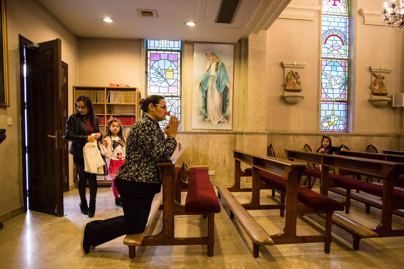 Farah (left), from Mosul, enters the church with her two daughters, Valentina, 7, and Faustina, 4. Farah was a civil engineer in Iraq, but now she and her husband are living off their savings, being unable to work in Jordan. She says the family have no plans to return to Mosul, saying it will still be too dangerous for Christians.