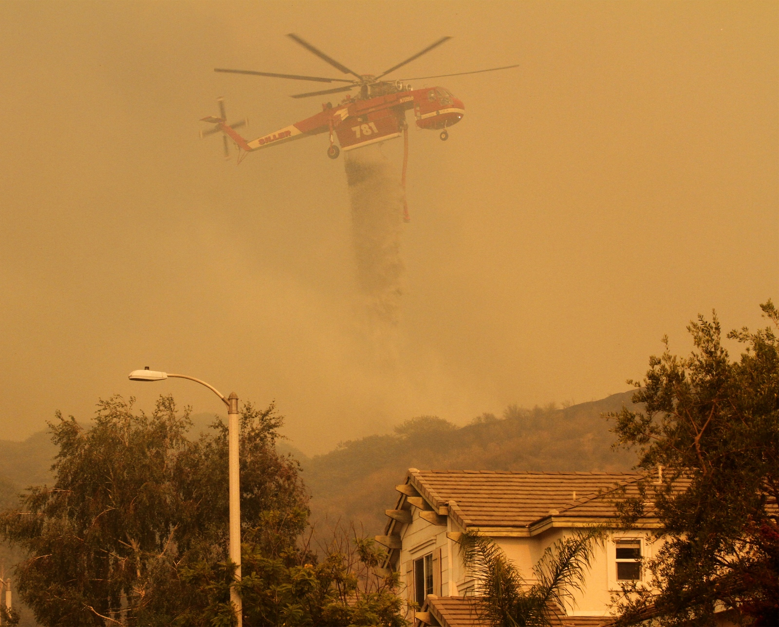 A helicopter drops water on the Sand Fire as it nears homes in the Fair Oaks Ranch neighborhood in Canyon Country on Sunday, July 24, 2016. More than 10,000 homes were evacuated during the height of the fire, and more than 18 homes were lost or damaged.