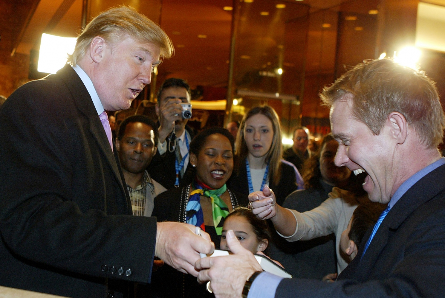 President Donald Trump signs a book to an unidentified supporter in New York.