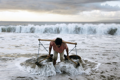 A man collects sea water at dawn to spray on to his salt fields in the Northeast of Bali Island in Indonesia.