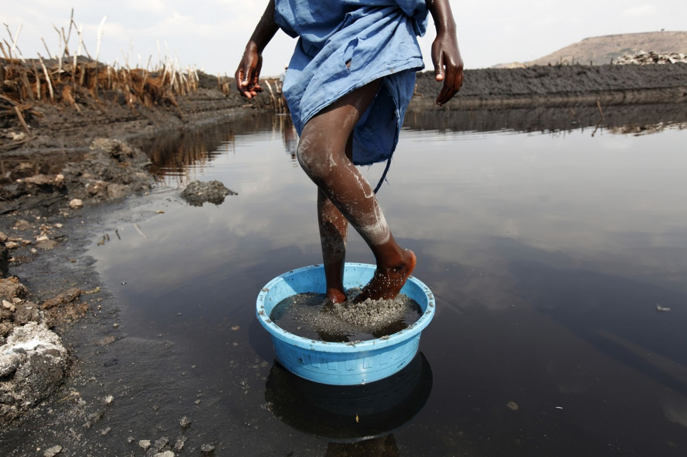 A girl grinds salt with her feet in one of the salt pans of Lake Katwe in Western Uganda.
