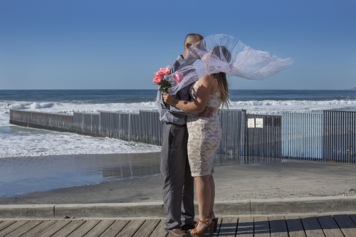Deported Christian Pastor Jonathan Ibarra and wife Gladys Lopez at their wedding photoshoot in front of the the U.S.-Mexico border fence in Playas de Tijuana, Mexico.