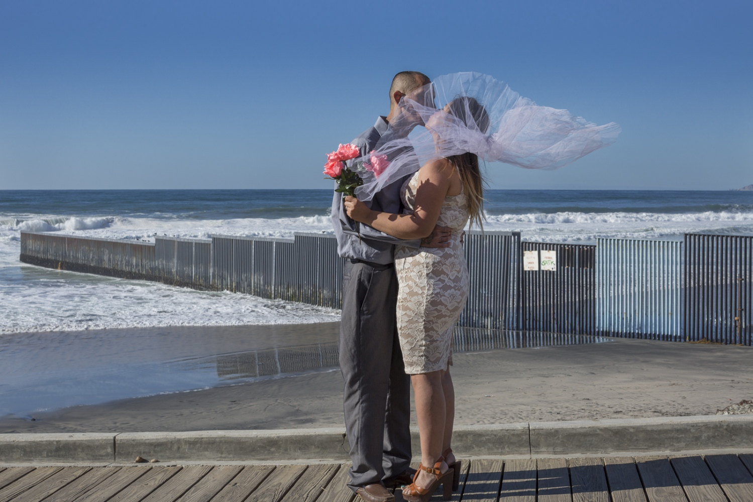 Deported Christian Pastor Jonathan and wife Gladys at their wedding photoshoot in front of the U.S.-Mexico border fence in Playas de Tijuana, Mexico.