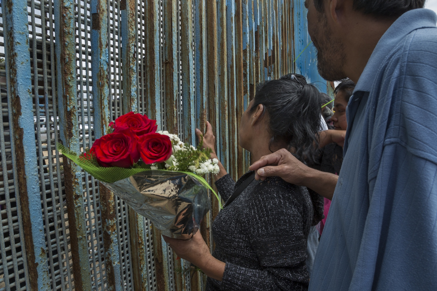 A woman talks to her children through the border wall on Mothers day 2016. An NGO distributed flower bouquets to all the mothers attending a binational event on the Tijuana side of the border.