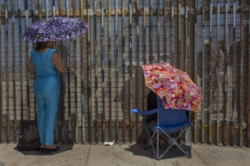 Two women meet with family members under the July sun at Friendship park, the only meeting place along the U.S.-Mexico border.