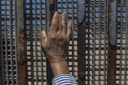 Anonymous hand at the border fence in Playas de Tijuana, Mexico. On the U.S. side of the fence, access to physically touch the wall is limited to a small area and the steel mesh is so tightly woven that people can barely touch fingertips.
