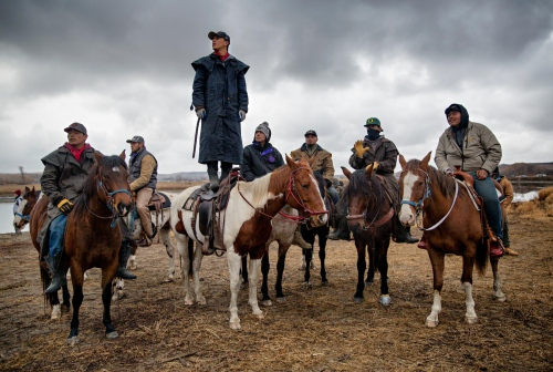 November 24, 2016- Cannon Ball, North Dakota, United States: A group of riders gather and watch the police line on top of the Turtle Hill where the Natives consider it to be sacred ground.