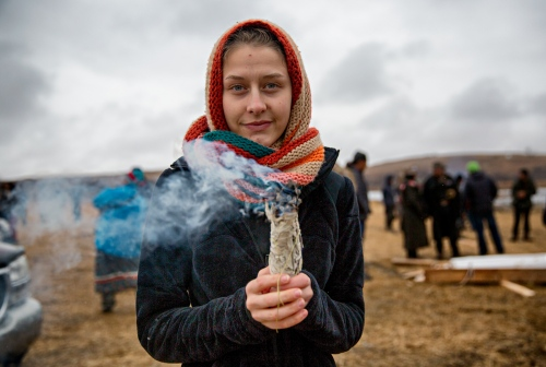 November 24, 2016 - Cannon Ball, North Dakota, United States: Aubrey Hart aka Hope, a new camp member, burns sage during the Thanksgiving day. Burning sage is for the cleansing of the body and the place surrounding it.