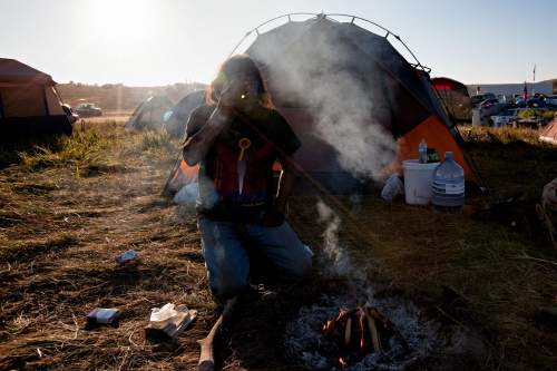 September 6, 2016- Cannon Ball, North Dakota, United States:Howard Eagle Show from South Dakota builds a fire before dusk in from of his tent at the Sacred Stone Camp, North Dakota.