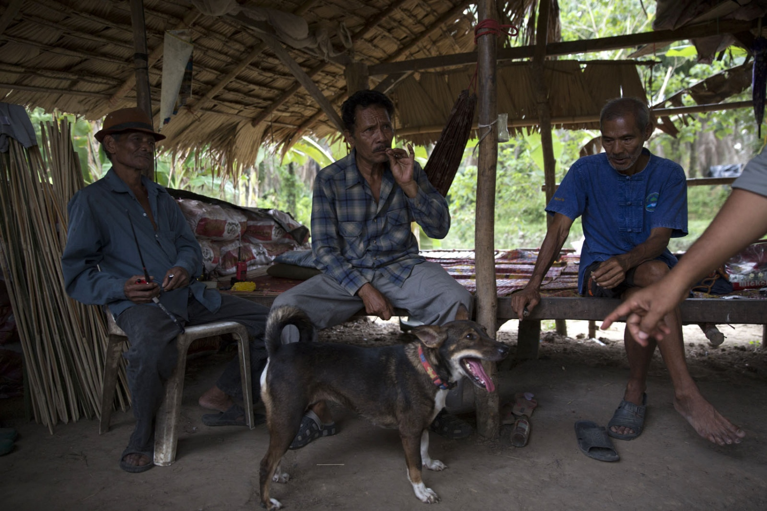 Prasit Rakhungthong, 61, (centre) one of the village leaders sits and talks with other village members in Bunker No.1 following the visit of local officials to discuss the construction of a water reservoir.
