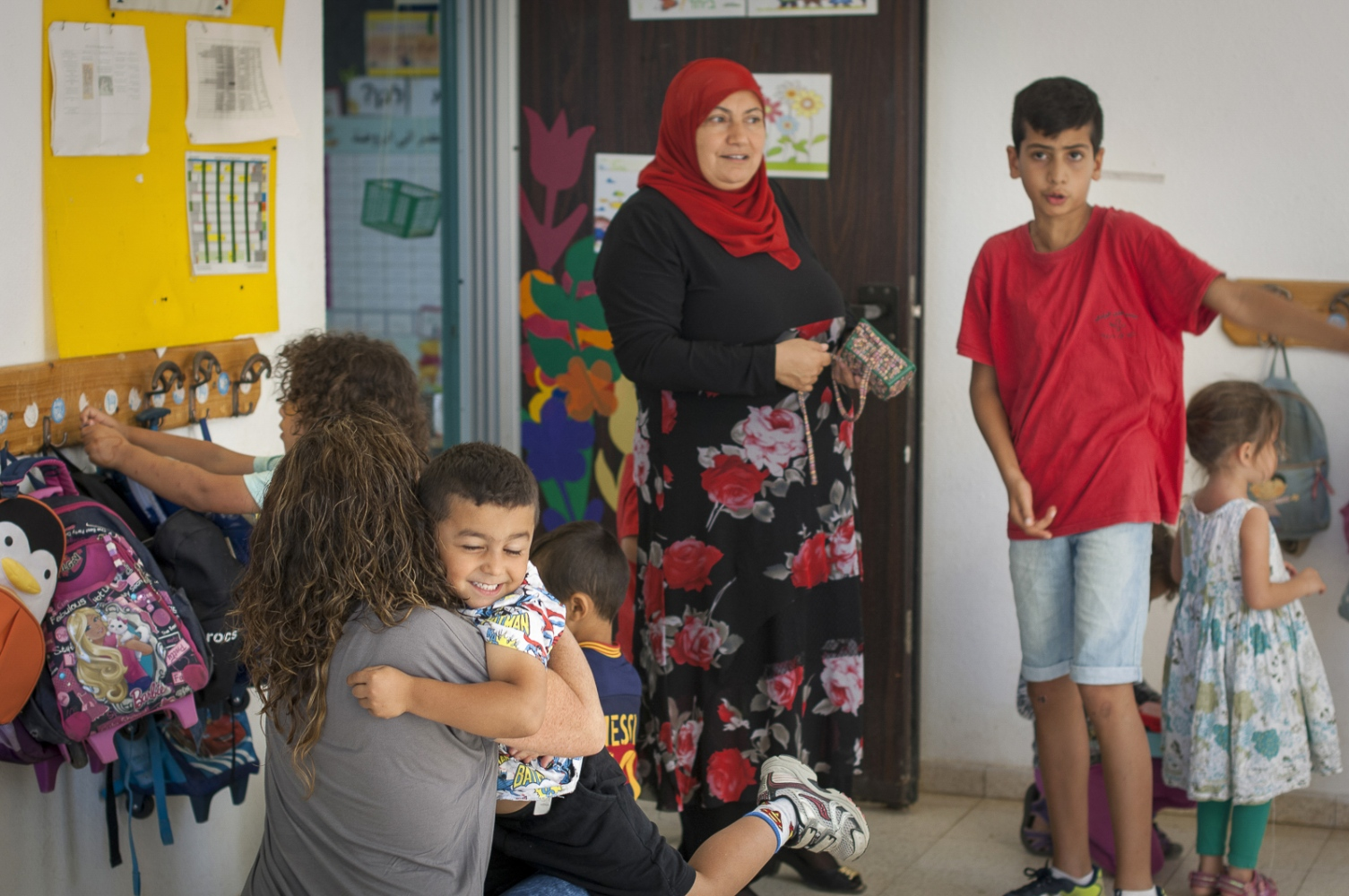 Kindergarden teacher Daisy Yaakov gets a hug from Bashar Abu Fane. Her co-teacher Layati Kaboha is in the background. Wadi Ara, Hand in Hand School, Kafr Qara, Israel.