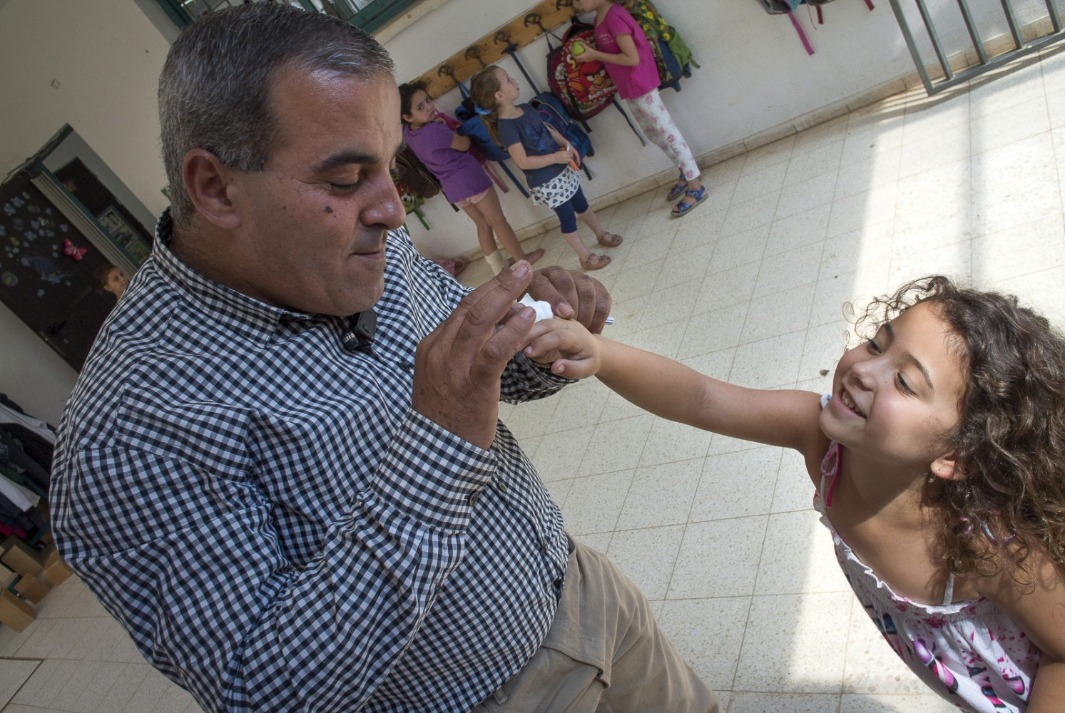 Wadi Ara Principal Hasan Agbaria consoles one of his Kindergarden students with a cut on her finger.