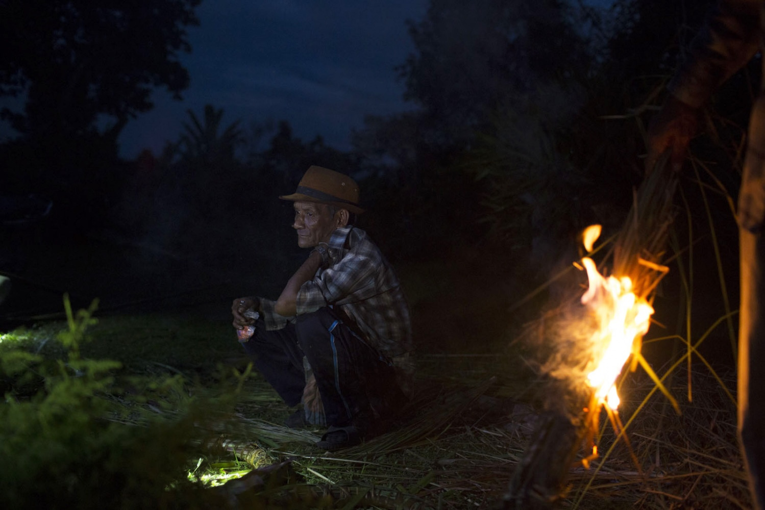 A man sits in the darkness outside a house with the only light coming from torches and fire at night time as there is no electricty in the village.