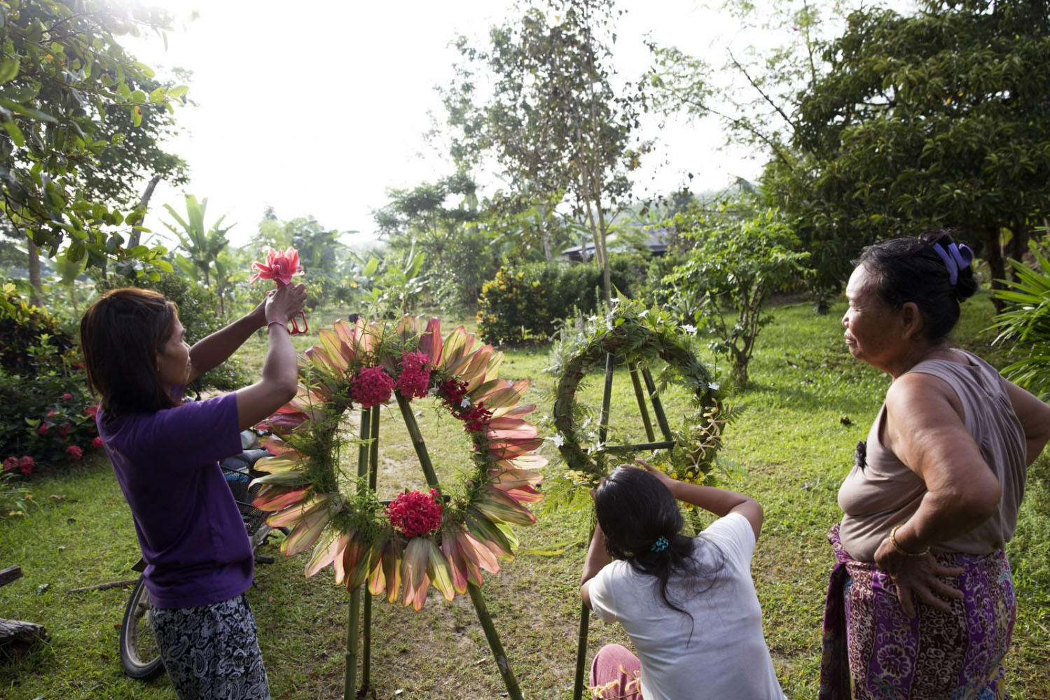 Women make reefs out of leaves and flowers as part of the memorial day of Klong Sai Pattana village in remembrance for each of the four people murdered during their prolonged fight to remain on the land.