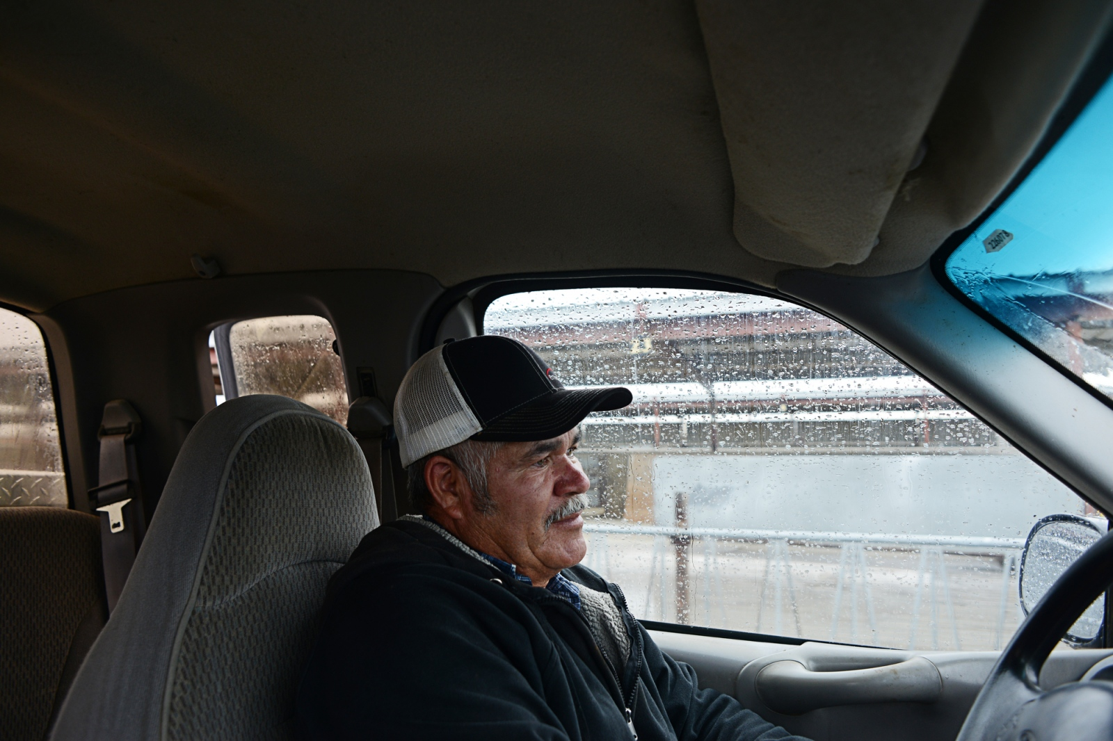 "Mr. Fregoso drives through the dairy farm he has worked on since the 1990s. ""When I first moved to Jerome [Idaho],"" Juan Fregoso, 59, says, ""it was a small town. They would look at me like I was a wild animal on the street. But I've lived a third of my life here. I love it. Humor has been essential. I've never missed a day to sickness. I hope they appreciate that when I go. Because it's not just a job."" ""Without each other? What are we?"" he says, holding out his hands. ""We need each other. ""I am Mexican first,"" Mr. Fregoso says, ""but I feel no security in Mexico. My heart's still down there. I support both lives [in Mexico and the USA]."" Juan Fregoso on the farm he has worked on since the 1990s as a self-described ""cow whisperer""."