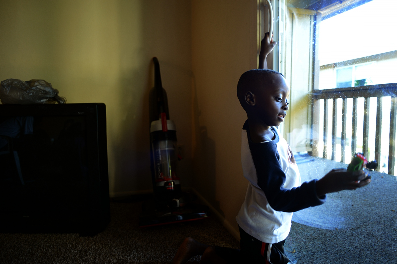 Mudather Geddo, 5, plays with a toy truck at his new home in Twin Falls, Idaho, after arriving from Cairo.