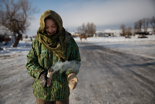 Heather Feather from Wisconsin burns sage and offers its cleansing capabilities to anyone who asks to be cleansed by its smoke.