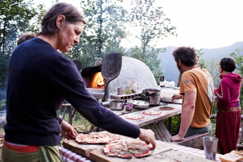Elves people cooking pizza in one of their typical clay oven.