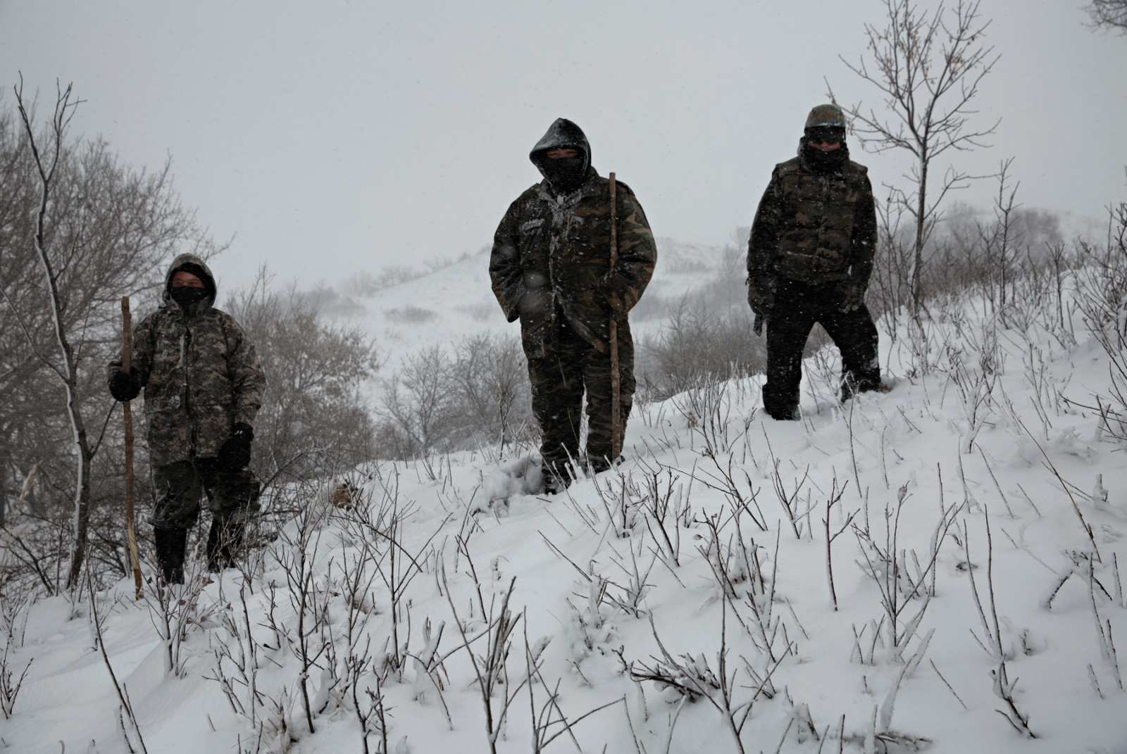 Three water protectors, who refused to identify themselves, stood on a hill while the veterans marched and made their presence known during a December blizzard.