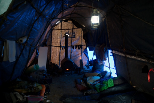 Inside a typical teepee made out of tree branches and a wood burning heater in the back. These communal teepees are used for gatherings,meditation, and sleeping.