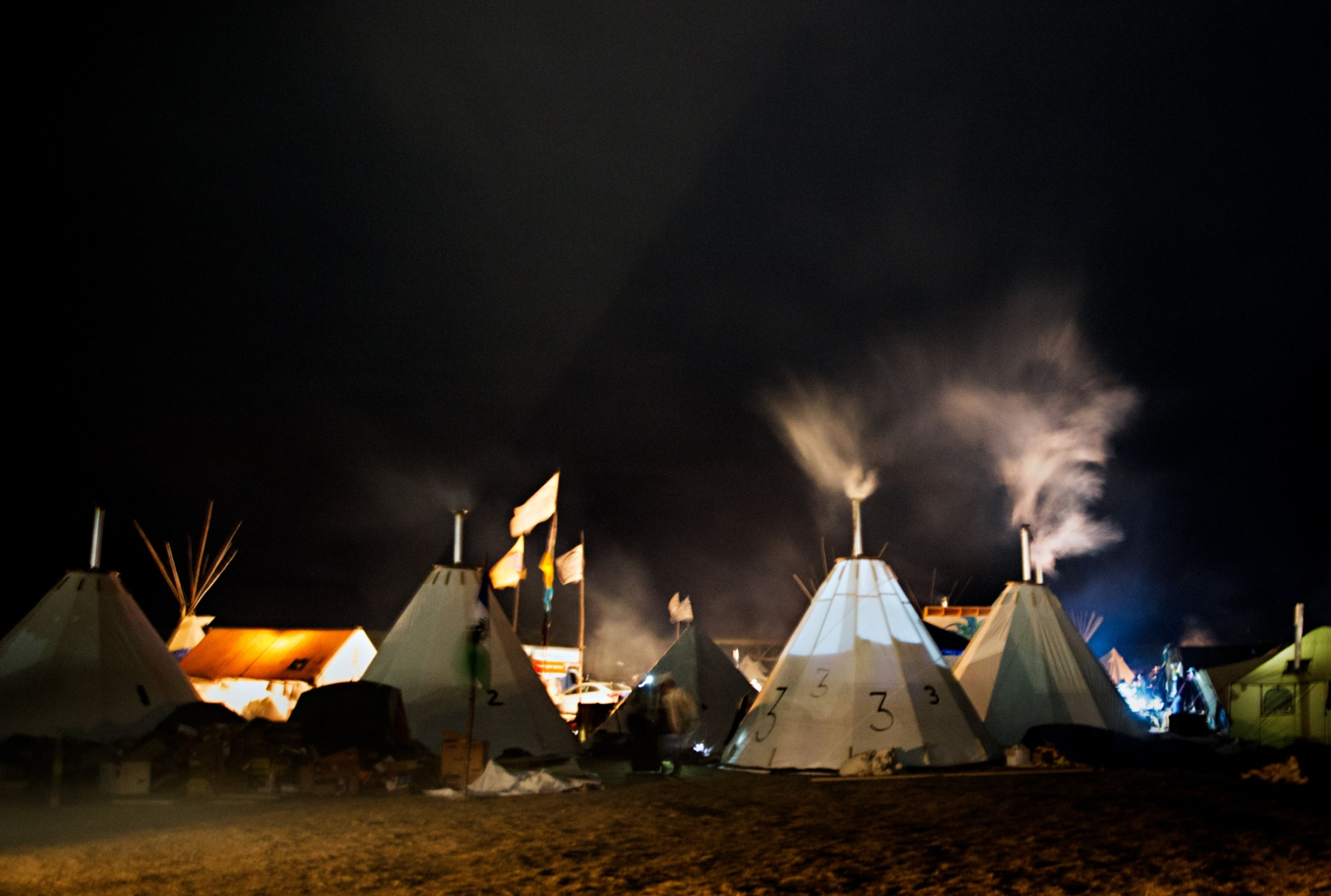 During the frigid November night the smoke from the teepees wood burning heater is appearant.