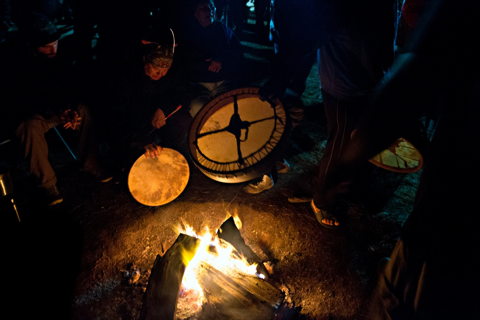 Drummers warm their instruments over the Sacred Fire at the Center Camp to help deepen the sound during the nightly songs and dances.