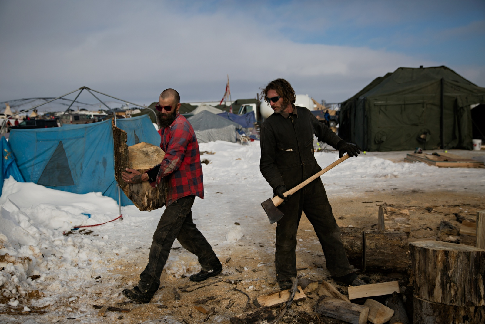 Aristeo Montasdioga (left), from Southern Arizona, and Timothy Jason-Reed (right), from Santa Monica, CA, chop wood for the community fire. The Army Corps of Engineers halted the Dakota Access Pipeline by denying the easement sought by the oil company to drill under the Missouri River.