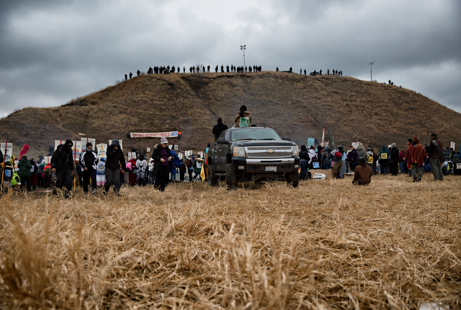 A police line on top of Turtle Hill, which the Sioux consider sacred ground, watch the Water Protectors below.