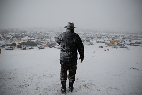"""During a heavy December blizzard, a man speaks on his phone on top of the hill better known as """"Facebook Hill,"""" where cell phone connection is at its best."""