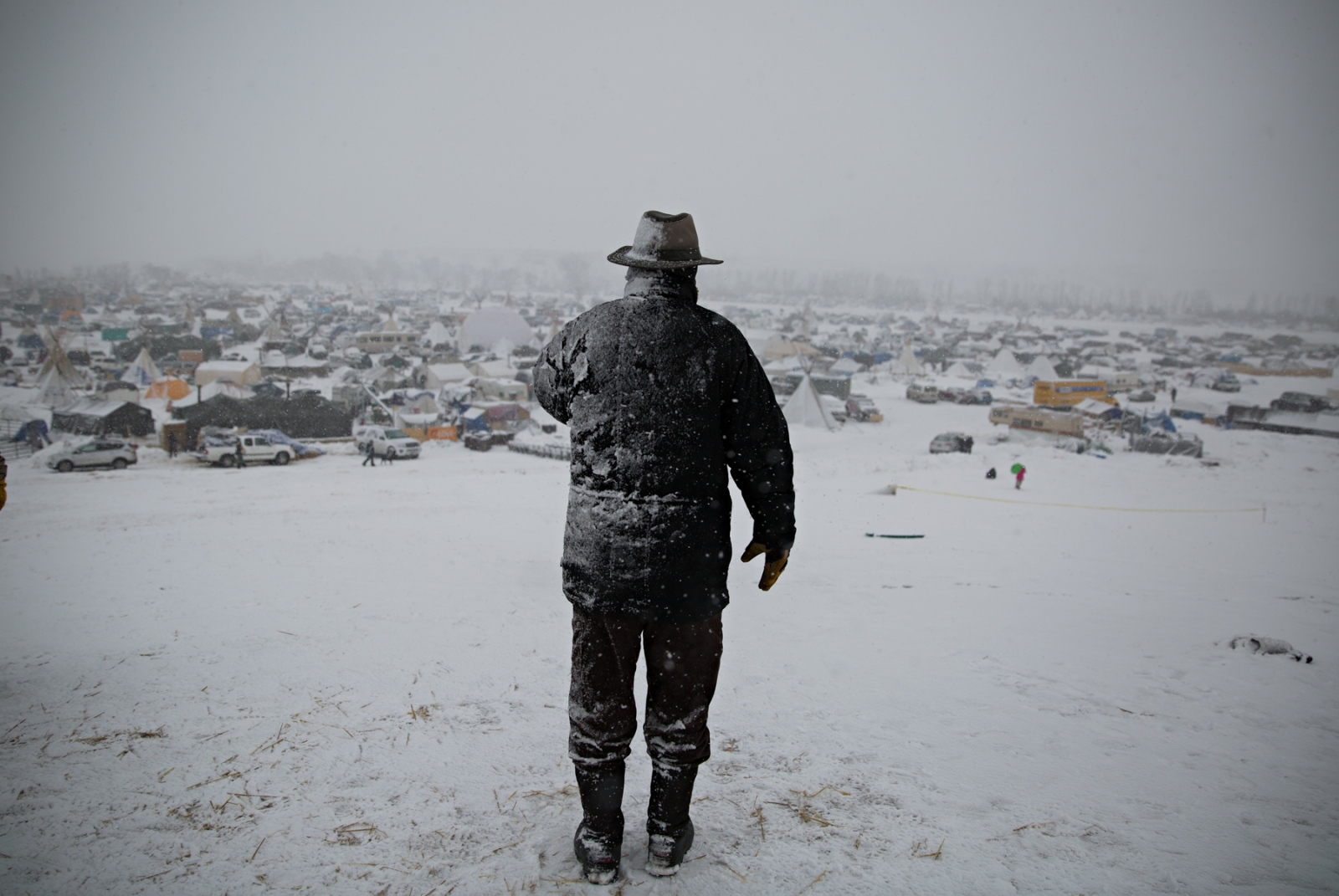 "During a heavy December blizzard, a man speaks on his phone on top of the hill better known as ""Facebook Hill,"" where cell phone connection is at its best."
