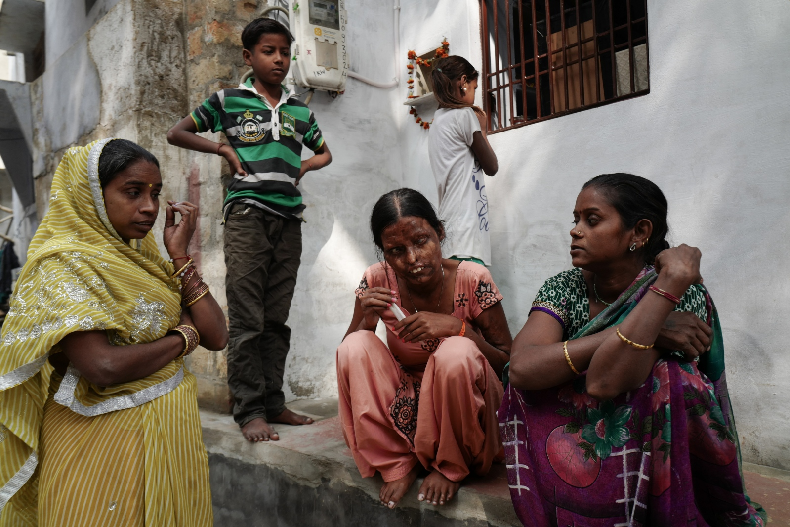 Agra, India. November 08, 2016. Neetu, sitting outside her house, talking with neighbours and friends.