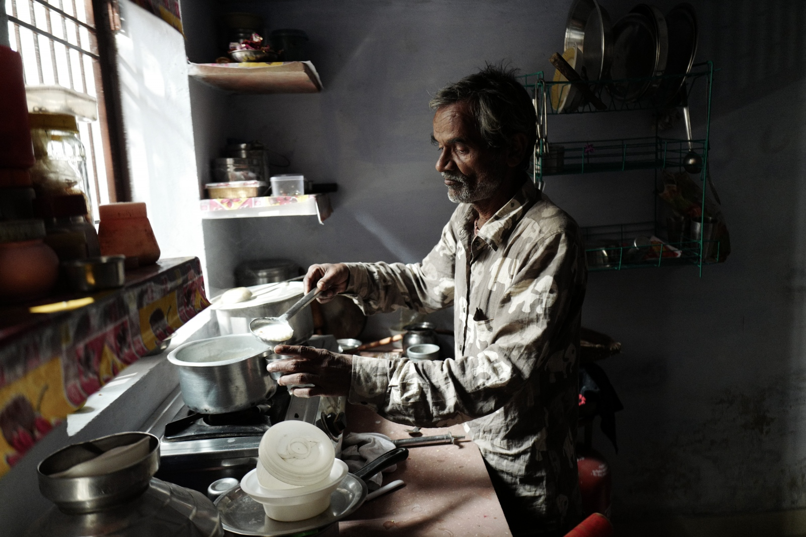 Agra, India. November 09, 2016. Indrageet in the kitchen preparing lassi for his daughter.