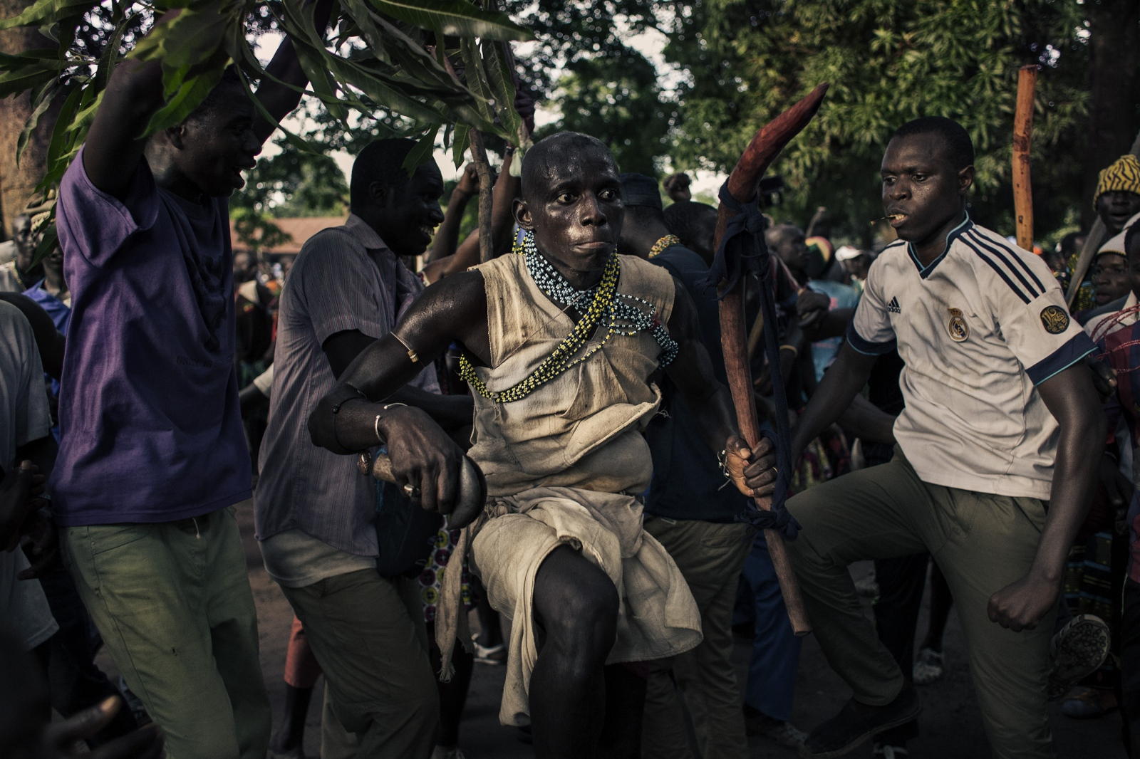 A boy dances before to enter to the forest, supported by his men relatives, in order to say goodbye to their family